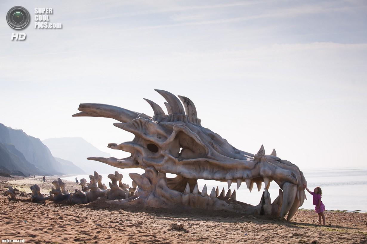 Великобритания. Лайм-Реджис, Дорсет, Англия. 15 июля. Панта Брэдбери у скульптуры в виде черепа дракона. (DANIEL LEWIS/blinkbox)
